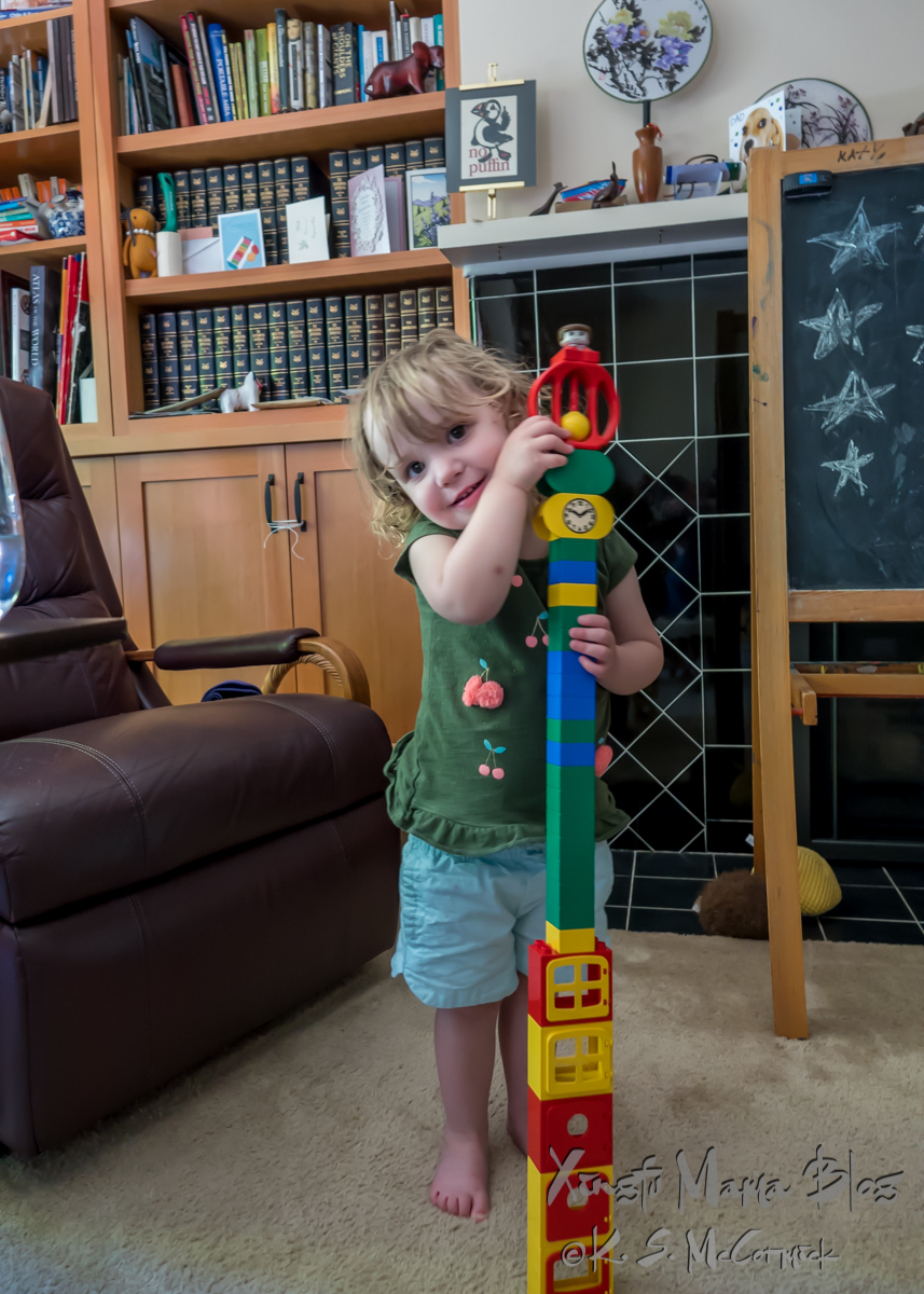 Toddler displaying a tower of duplo blocks that she built.
