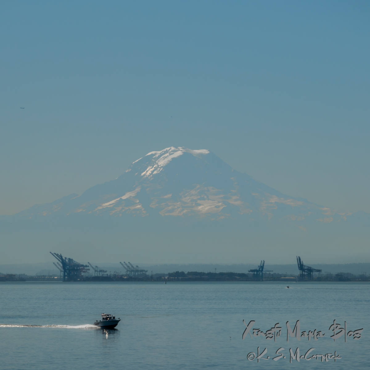 Baby blue morning: view of Mount Rainier and the port of Tacoma with a speed boat in the foreground. Photo taken from a ferry on the Puget Sound