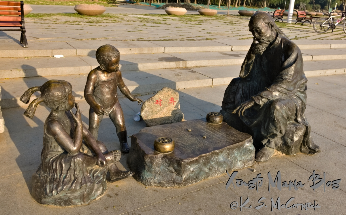 Bronze sculpture of a girl playing go with her grandfather as her little brother watches. By the Mihe River in Shouguang, China,