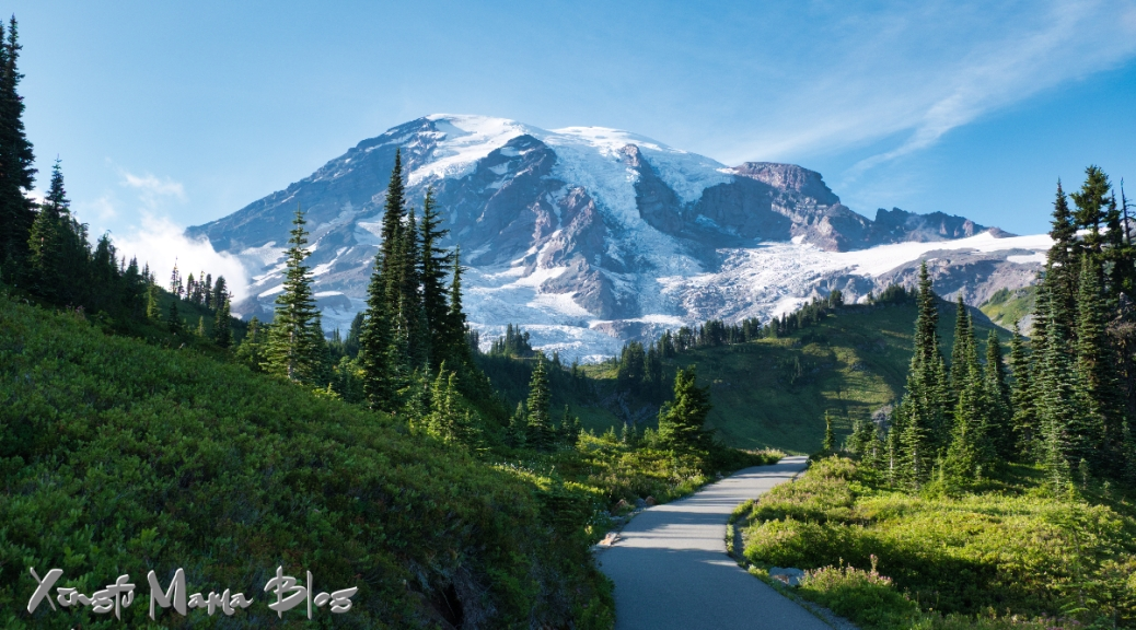 Mount Rainier rises beyond a paved trail at Paradise.