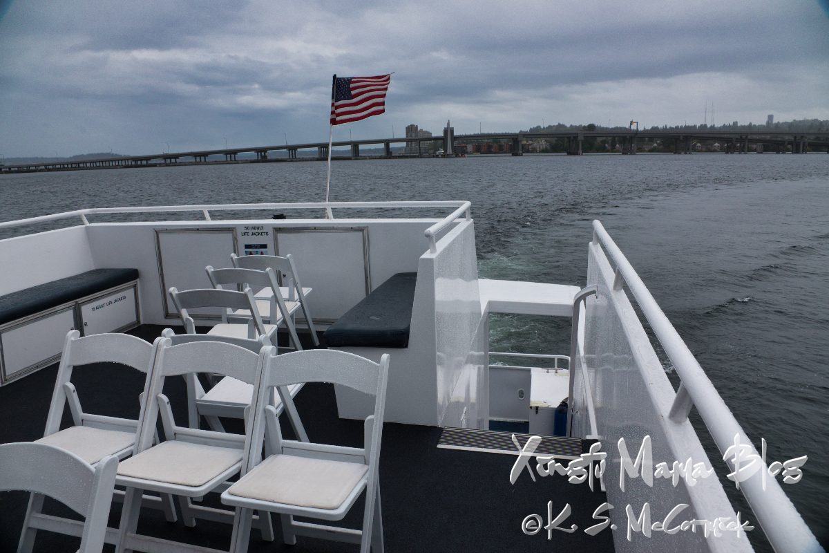 Cloudy skies and the western high rise of Washington SR 520 bridge in the background, the US flag, folding chairs and wet built-in benches on an Argosy history cruise.