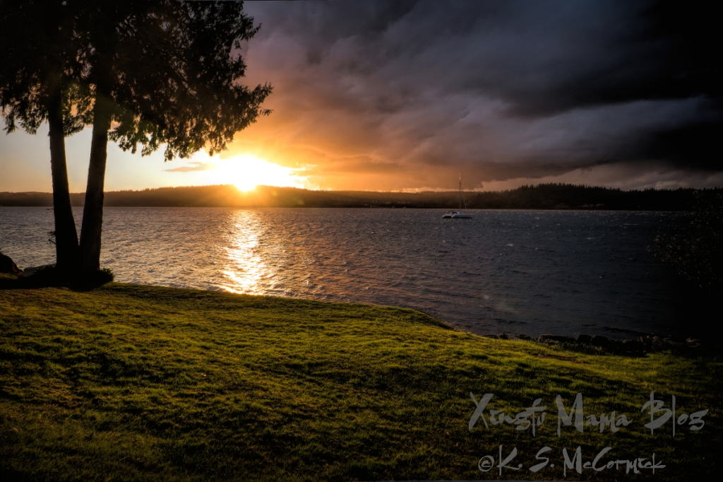 Storm clouds moving toward the sun setting over Puget Sound, taken on Vashon Island in Washington State.