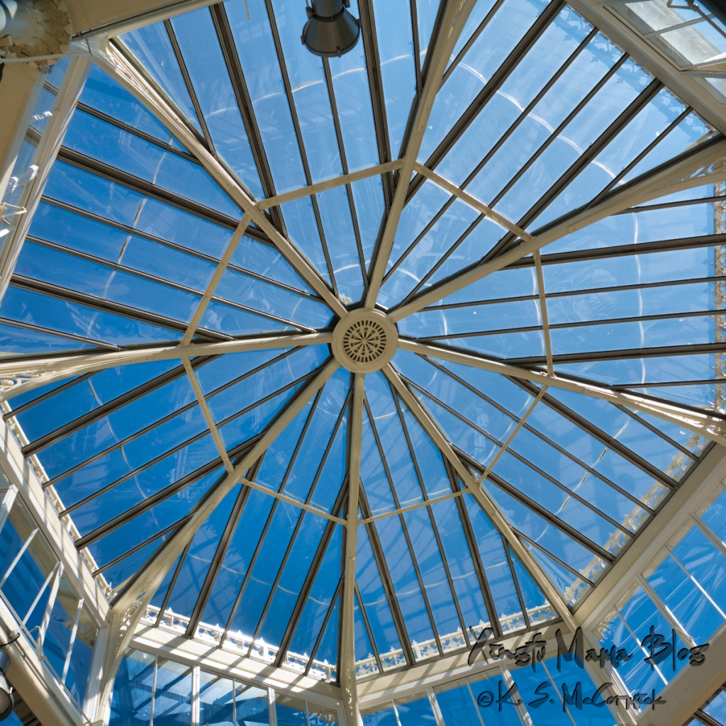 The blue sky shows through the steel structure of the roof of the temperate house at Kew Gardens in London, England.