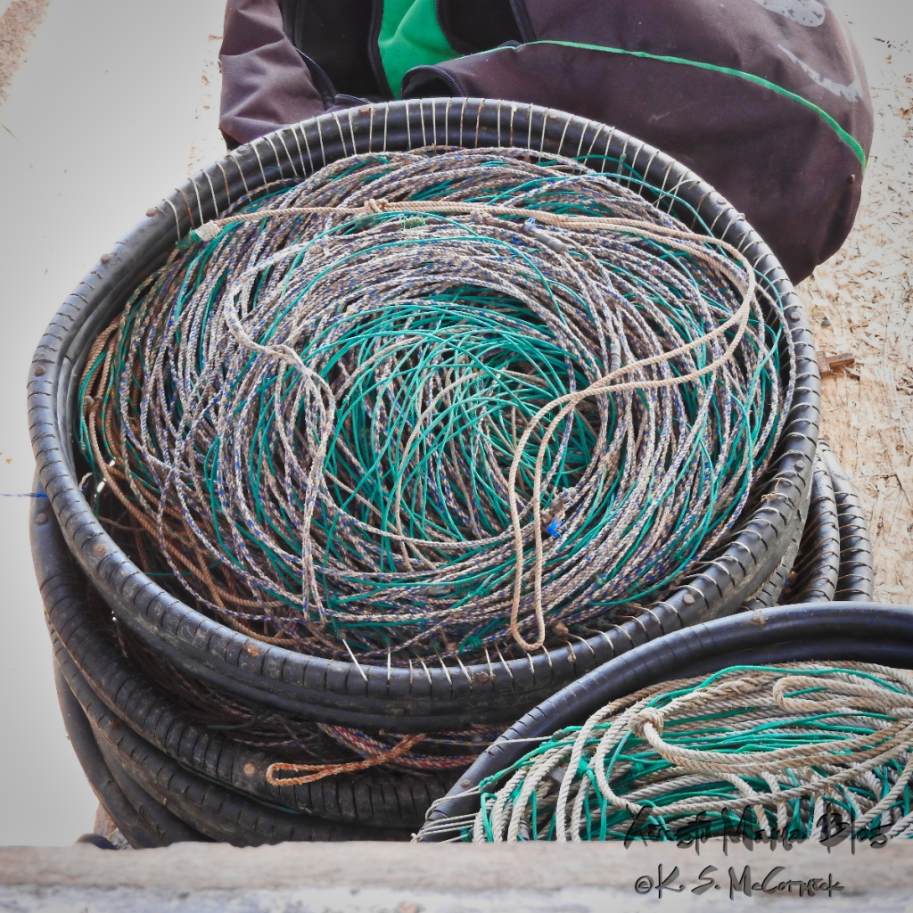 Coiled fishing lines in a rubber basket with the hooks attached to the side at the fisherman's pier in Punte del Este, Uruguay.