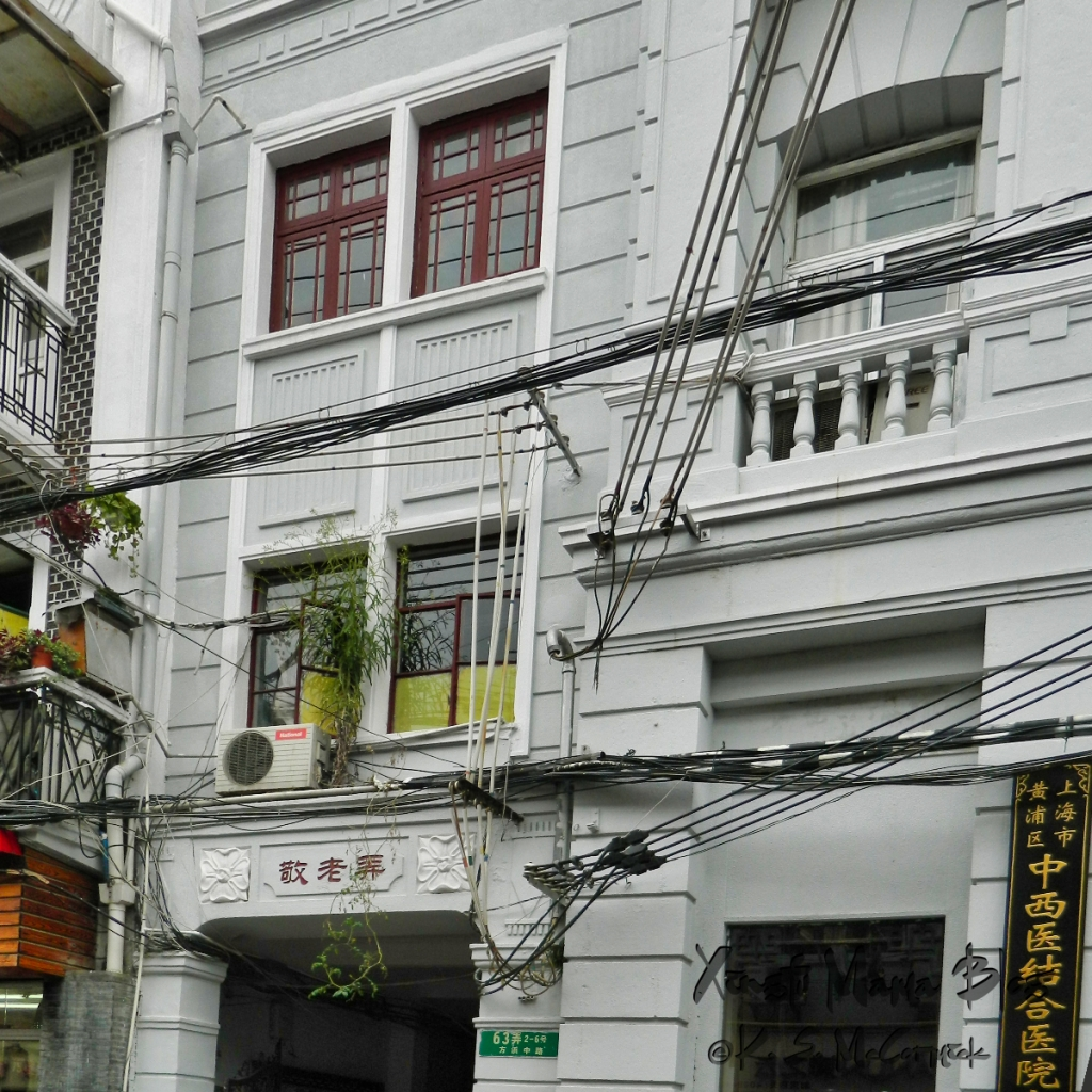 Photo of a twon house in Shanghai with a lit of communication and power lines going in and out of it.