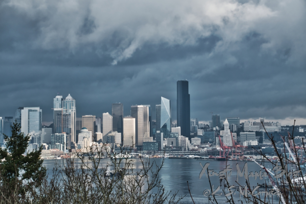 Modern Seattle skyline illuminated by a passing sun break on a gray winter day.