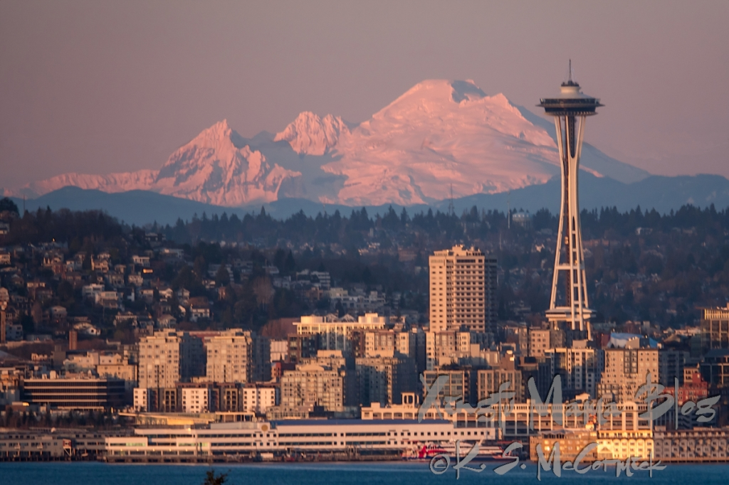 Seattle Space needle with Mount Baker in the background, illuminated by the sunset on Christmas Eve.