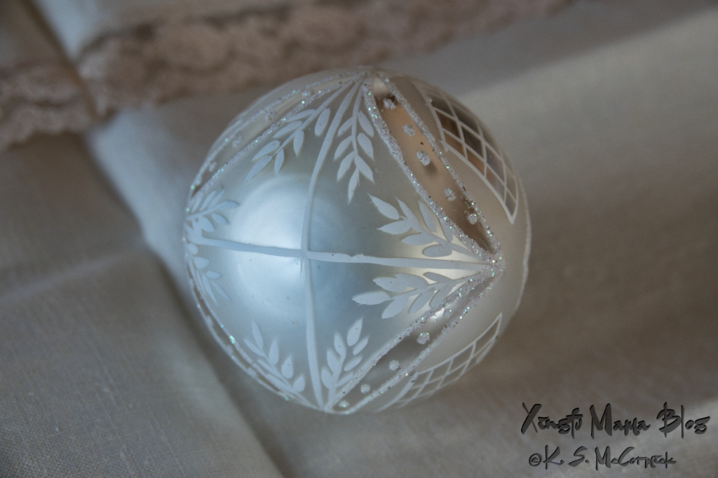 Christmas ornament on linen, white-on-white still life for the holidays.