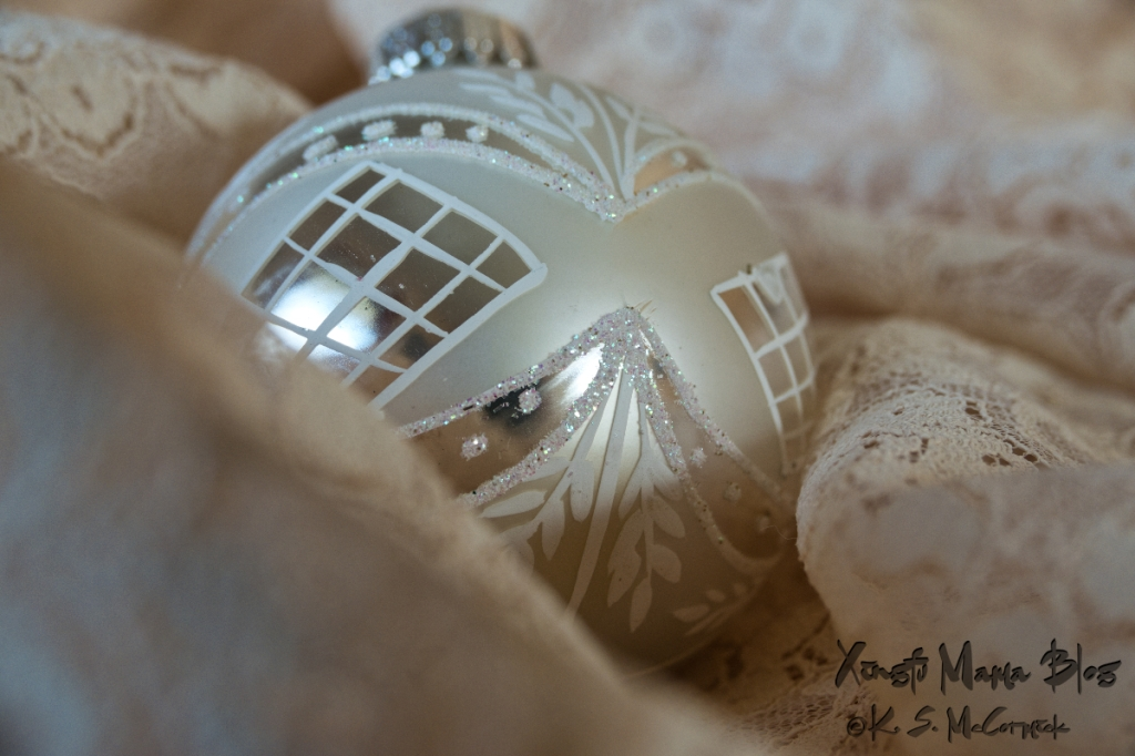 Old lace and a Christmas ornament in a white-on-white still life.