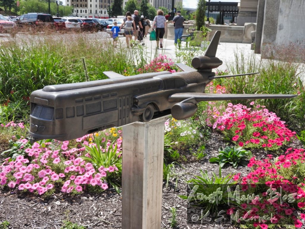 Bronze sculpture combining three modes of transportation: street car, automobile and aeroplane, in Kansas City Missouri.