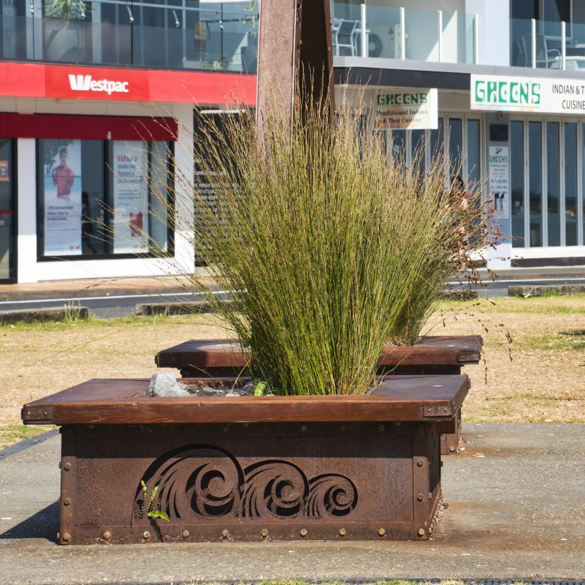 Planter box benches with the swirly pattern that can be either waves or ferns.