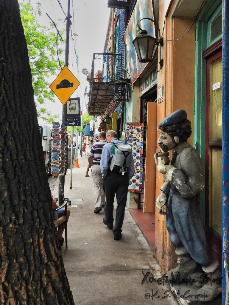 Side view of a sculpture of a man holding a cup of yerba mate and looking out from a doorway in La Boca district of Buenos Aires, Argentina.