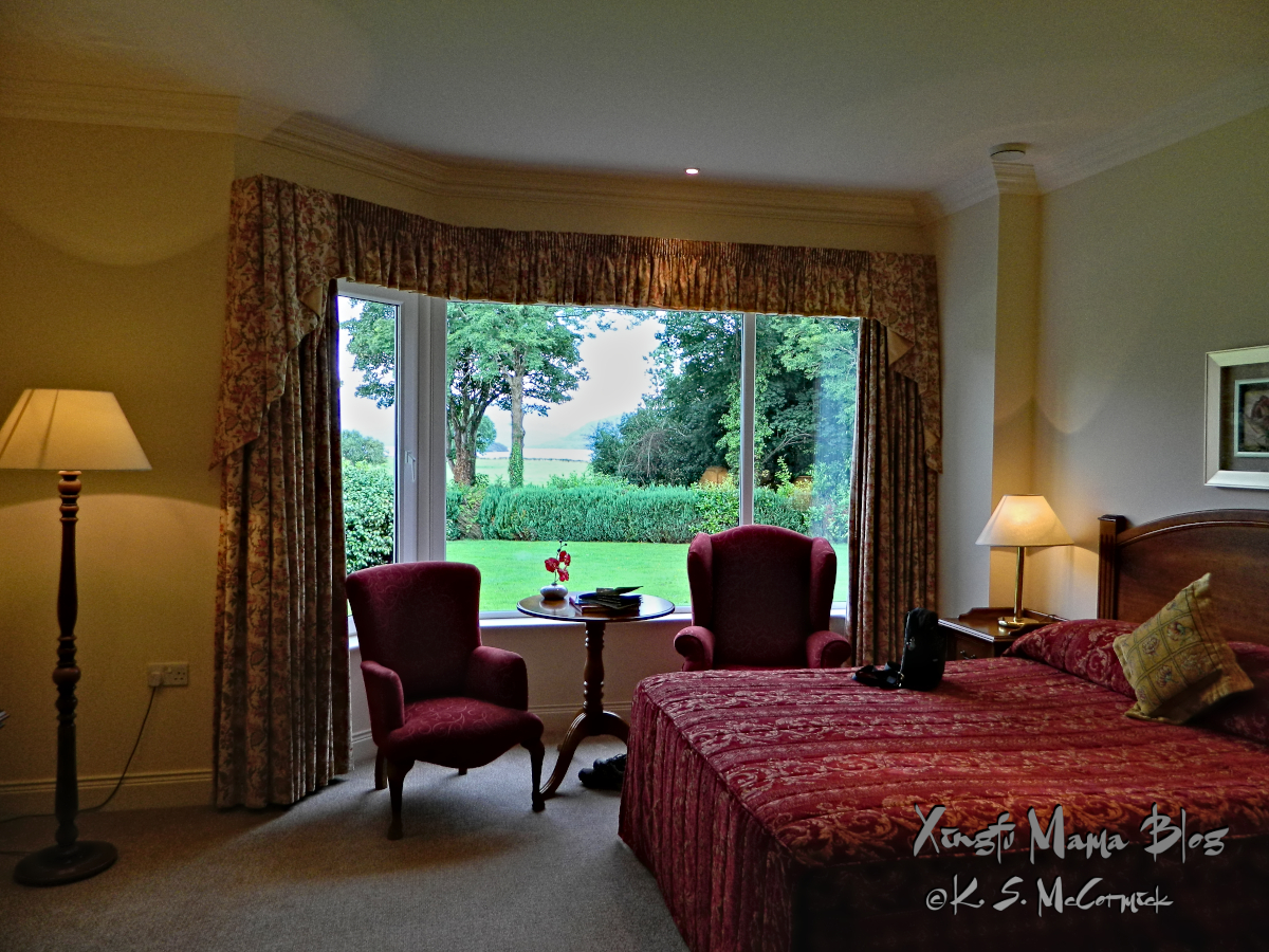 Red wing chairs beside a bay window with a view out toward Lake Killarney.