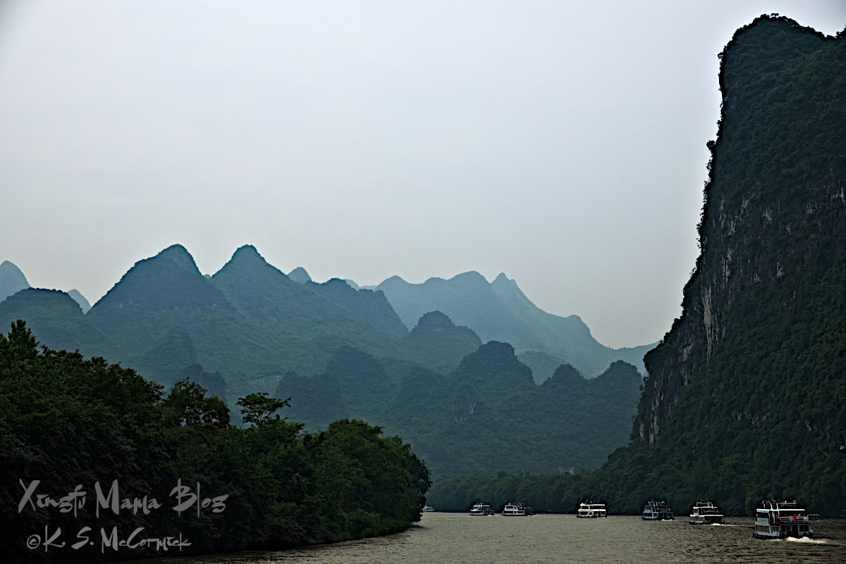A line of river cruise boats on the Li River in Guilin, China.