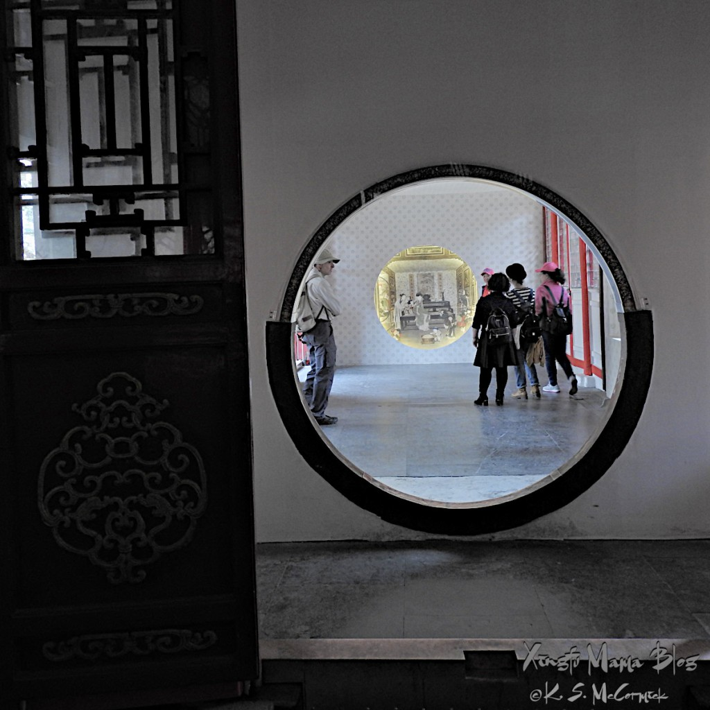 A round wall paintnig framed by the round moongate type entrance to the room. Photo taken in the Forbidden City in Beijing, China.