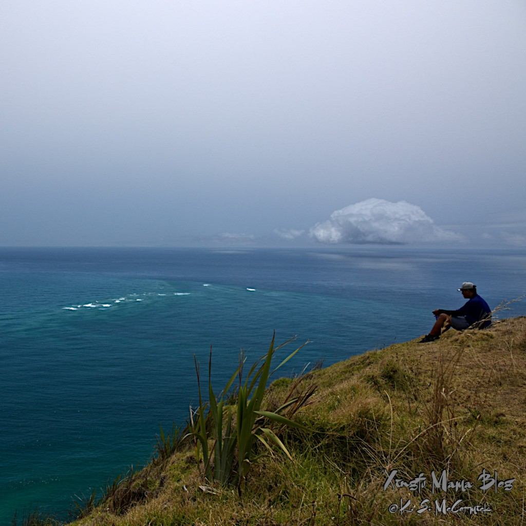 A man sitting and watching the water at Cape Reinga, toward the intersection of the Tasman Sea and the South Pacific Ocean.