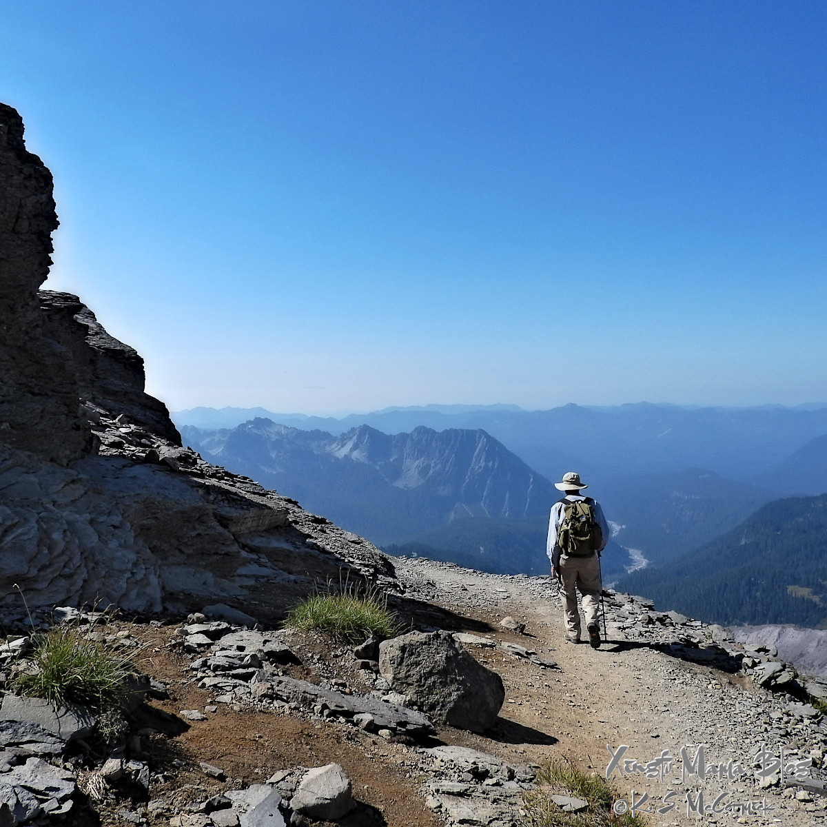 Hiker walking on a narrow trail with views out to the Cascade Mountains.