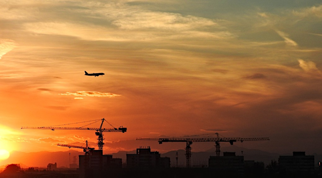 Construction cranes at the Beijing Capital Airport and the mountains beyond it at sunset.