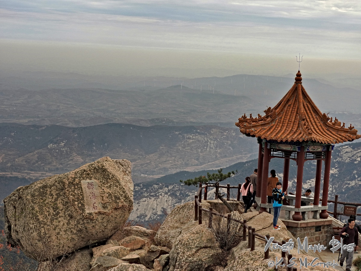 An oriental pavilion beside a large boulder precariously positioned at the top of Yishan in Shandong Province, a misty view out into the distance.