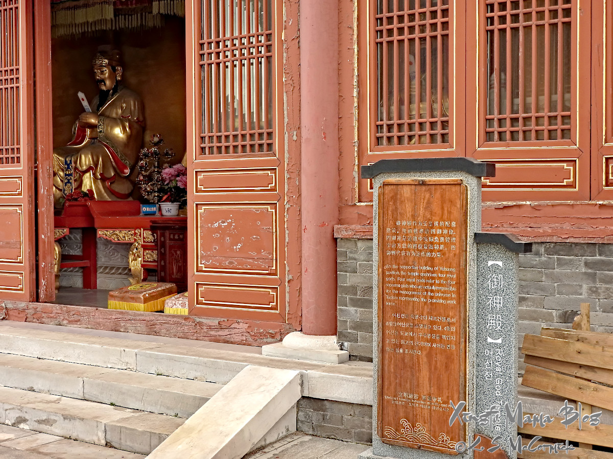 A golden statue of a god is visible through the door of a temple at the top of Yishan, in Shandong Province.