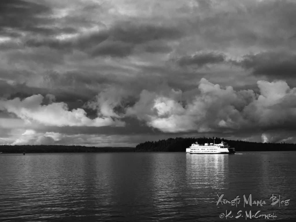 Black and white of a white ferry traversing the peaceful waters of Puget Sound with dramatic clouds overhead.