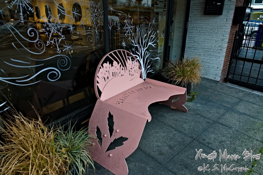 Artistic pink metal bench decorated with flowers.
