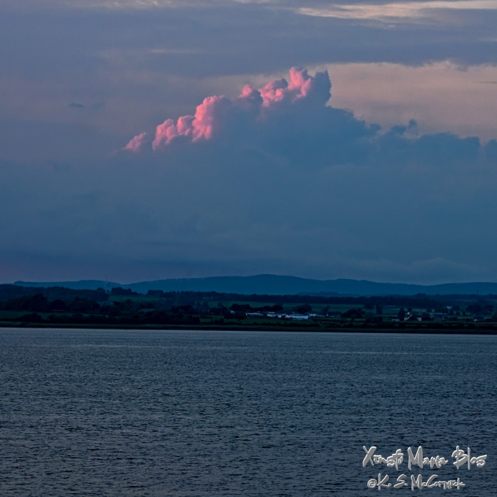 Setting sun lighting up a pile of clouds in a view across Solway Forth toward Scotland around mid-summer.