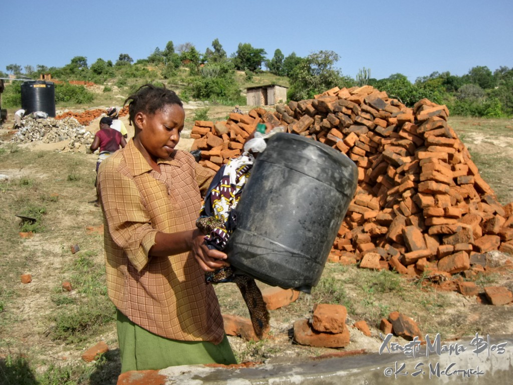 Kenyan woman emptying a jerrycan of water.