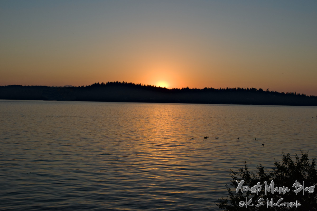 The sun setting over the Kitsap Peninsula, viewed from Vashon Island in Puget Sound.